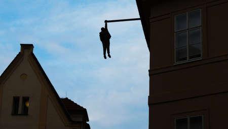PRAGUE, CZECH REPUBLIC - Oct. 6, 2015: Zigmund Freud statue hanging on the roof of building in Prague. Modern city art. Editorial