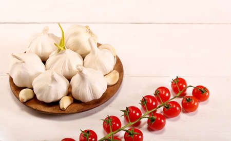 Garlic. sliced garlic, garlic clove, garlic bulb, branch of cherry tomato in wooden plate on vintage rustic white wooden background.