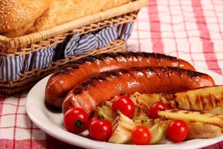 Saucisses barbecue grillées avec légumes, épices et pain en plaque blanche sur table Banque d'images