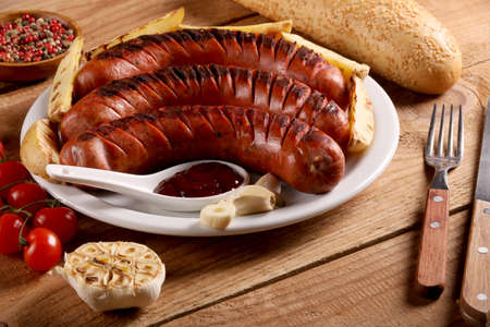 Grilled bbq sausages with vegetables, spices and bread in white plate on wooden table
