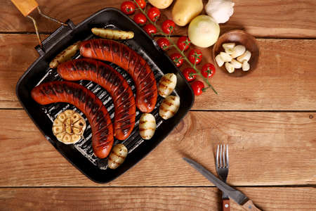 Grilled bbq sausages with vegetables and spices in a pan on wooden background. Top view