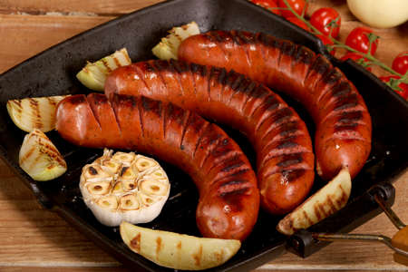 Grilled bbq sausages with vegetables and spices in a pan on wooden background
