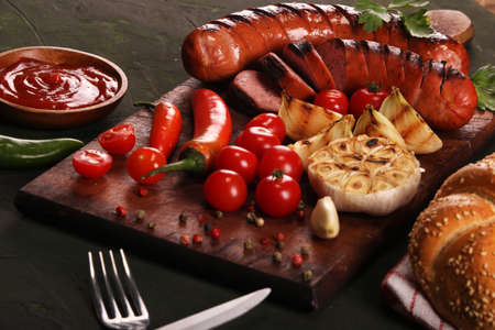Grilled bbq sausages with vegetables, spices and bread on wooden cutting board background