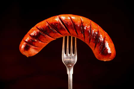Extreme close-up Grilled sausage on a fork isolated on a black background