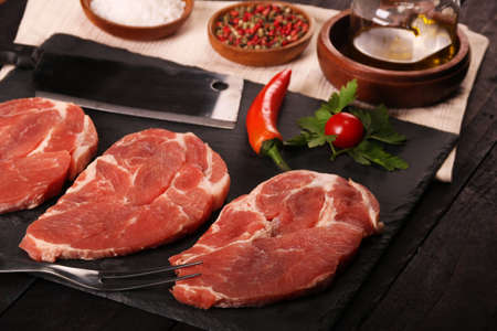 Raw pork meat steak with vegetables, peppers, tomato, salt, rosemary and spices cooking over stone cutting table. Stock Photo