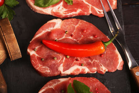 Raw pork meat steak with vegetables, peppers, tomato, salt, rosemary and spices cooking over stone cutting table. Top view. Stock Photo