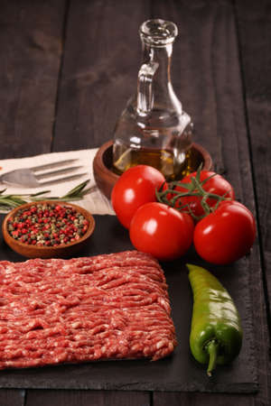 raw minced meat on plate, ingredients for burger with tomato, pepper, onion, spices and seasonings on black wooden background. Banco de Imagens