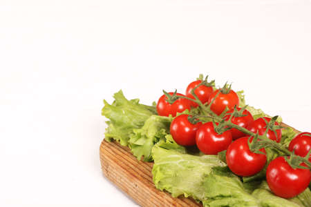 Ripe fresh Juicy organic brunch of cherry tomatoes on cutting board with Green Lettuce on a white wooden table