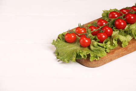 Ripe fresh Juicy organic brunch of cherry tomatoes on cutting board with Green Lettuce on a white wooden table. Copy space
