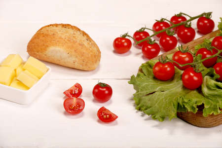 Ripe fresh Juicy organic brunch of cherry tomatoes on cutting board with Green Lettuce, bread, butter on a white wooden table