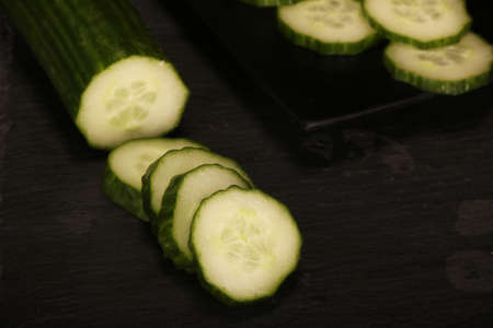 Fresh sliced cucumbers on black cutting board and wood rustic background. Flat lay pattern of green cucumbers on table, close-up Imagens