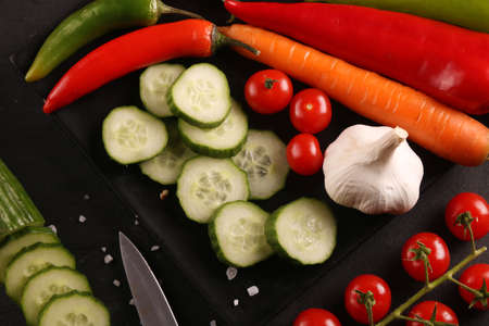 Healthy food. Vegetables on a black plate and stone cutting board and wooden black table background. Imagens