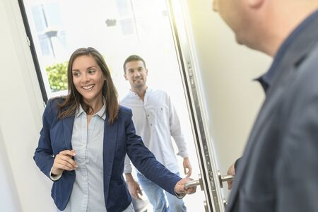The real estate agent welcomes his young clients for a visit Stock Photo