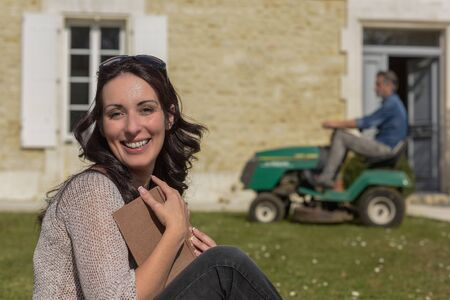Wife takes advantage of husband to pass lawn tractor to relax and read