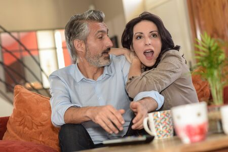 middle-age couple watchs a soccer match on TV