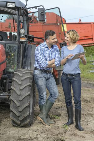 Couple of Farmer analyses the harvesting in a field over a digital tablet