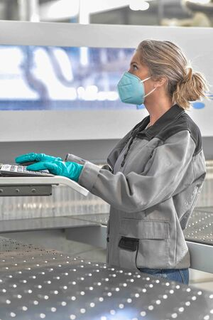 Female engineer is operating on a digital pannel in the company and wearing protections against coronavirus Standard-Bild