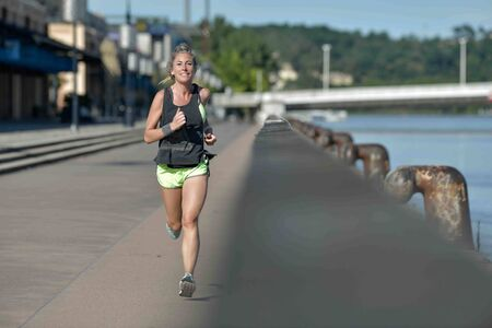Smiling woman during her running cession along the river