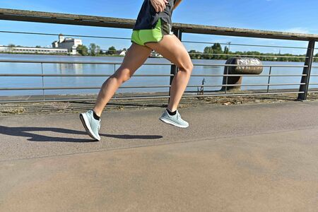 view of woman legs during a running cession along the river