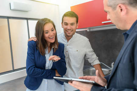 Happy couple talking to a real estate agent about buying the flat Stock Photo