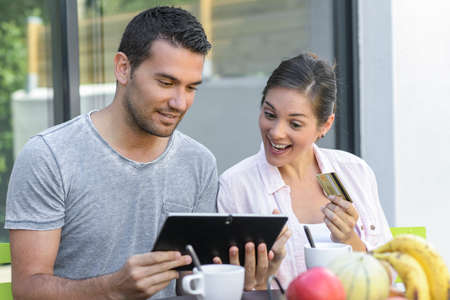 Happy couple using a tablet and paying online