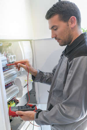Electrician tests circuit breakers in a electrical panel