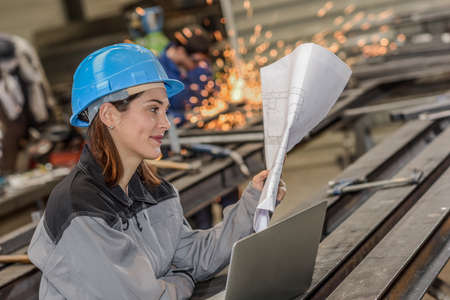 Happy female worker reads a blueprint in metal factory Stockfoto