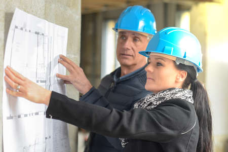 Architect and his assistant are checking a blue-print leaning on the wall