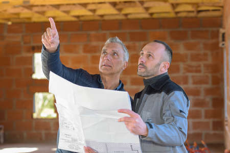 Architect and contractor looking at plans on a building site