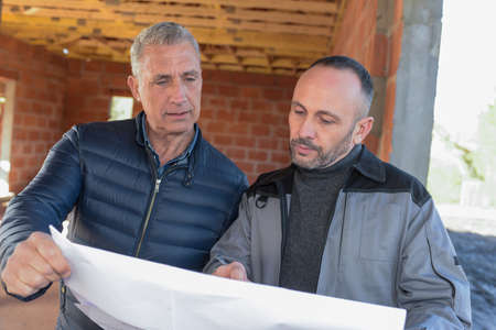 Architec and engineer looking at plans on a building site