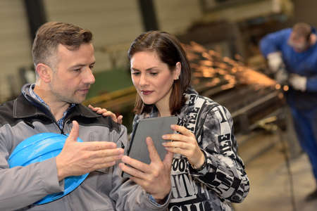 Female factory boss is not sure about what his worker is showing to her