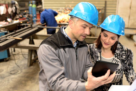 Worker and female manager are looking at a tablet in a factory 免版税图像