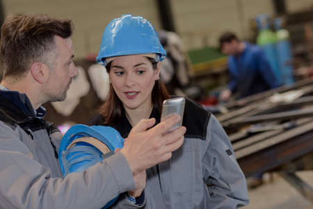 Male worker shows his colleague a mobile-phone in the factory