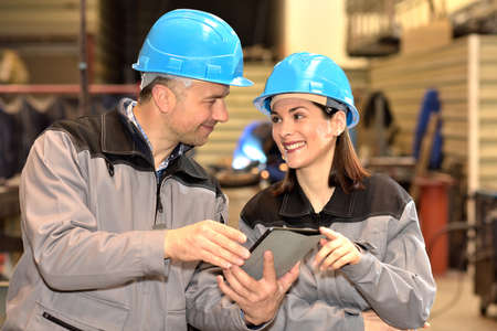 Happy workers using a tablet are sharing their positive ideas in the factory