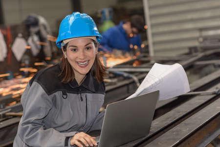 Confident woman engineer checks a blueprint at work