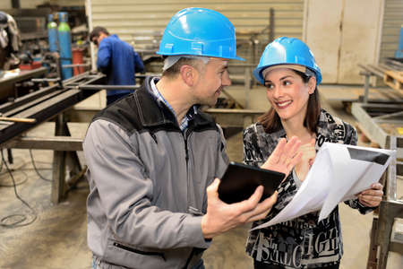 Both workers wearing hardhats are comparing notes and tablet in the factory
