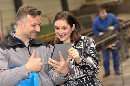 Factory coworkers agree on a new idea, showing thumbs up