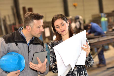 Confident businesswoman is showing a blueprint to his male worker