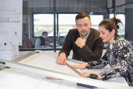 Supervisor checks her female architect assistant's work
