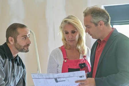 Discussion around the plan of an architect between the construction manager and the craftsmen involved in the renovation of a house