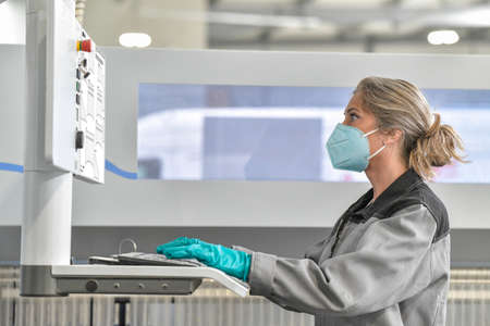 Female engineer is operating on a digital pannel in the company and wearing protections against coronavirus