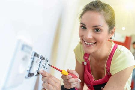 Female technician is screwing an electric socket Reklamní fotografie
