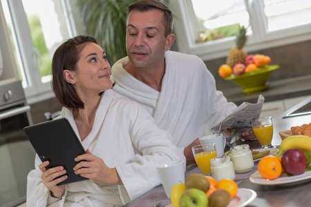 Couple in bathrobes are reading news on newspaper and on the tablet in the kitchen
