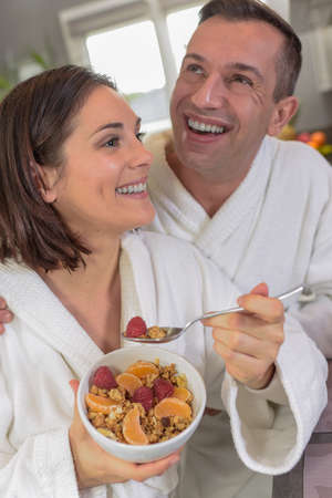 Young couple in bathrobes takes a healthy breakfast in the kitchen