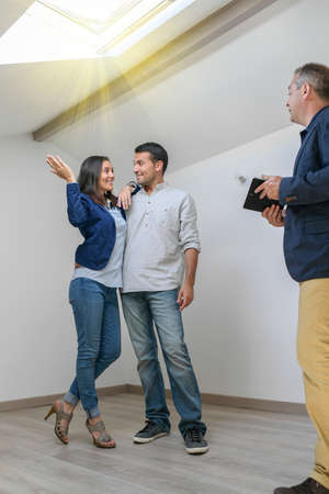 Happy couple visiting a flat with a roof windows in an attic room