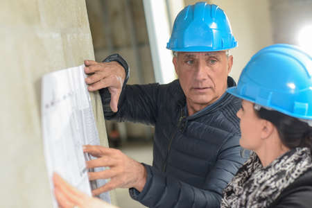 Architect and his assistant are checking a blue-print leaning on the wall Stok Fotoğraf - 160437955