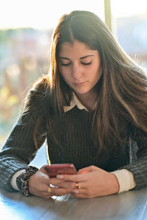 Female teenager student is browsing on his mobile at home or chatting with a friend on a social network with a mobile application Reklamní fotografie