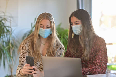 Young female students are working together at home and are wearing protective mask due to the covid-19