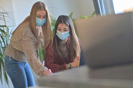 Young female friends are stuying together on their computer at home and are wearing protective mask due to the covid-19