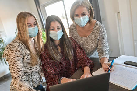 Twin sisters and their mother wearing protective mask and watching a webinar on a laptop at home during lockdown due to covid-19